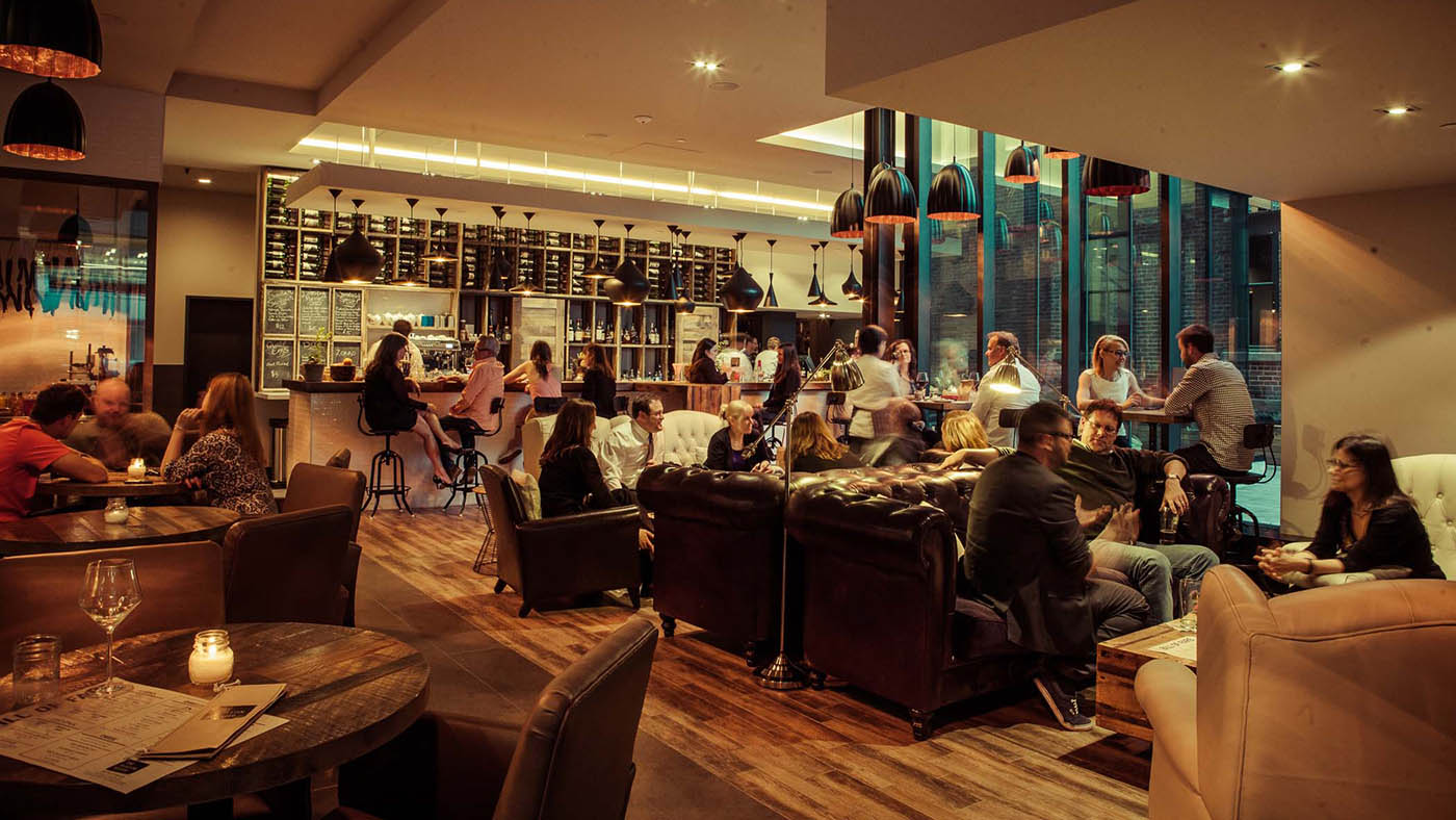 Interior of restaurant warmly lit and groups of people having fun and eating.